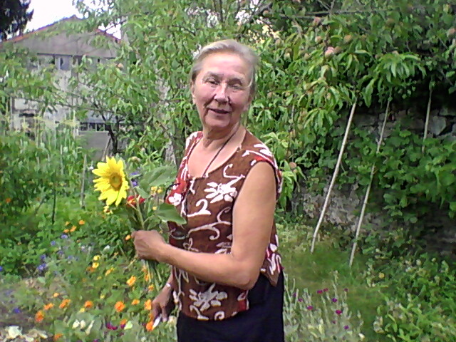Sini Manninen in her garden, holding a flower